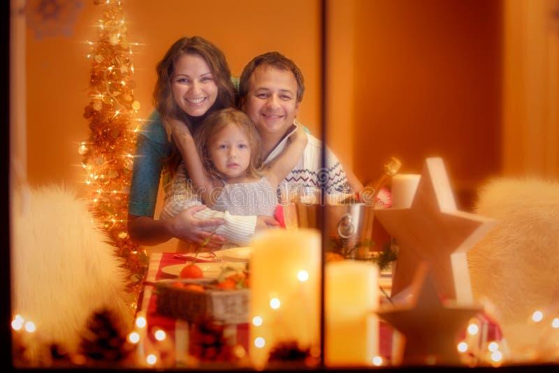 Ritratto di Natale di una famiglia di tre felice a casa fotografia stock