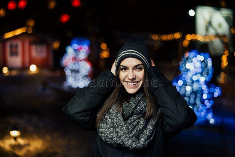 Ritratto di notte di bella donna castana che sorride godendo dell'inverno in parco Gioia di inverno Vacanze invernali Emozioni po fotografie stock