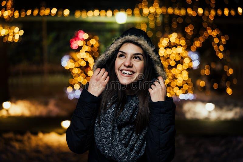 Ritratto di notte di bella donna felice che sorride godendo dell'inverno e dell'aria aperta della neve Gioia di inverno Vacanze i fotografia stock