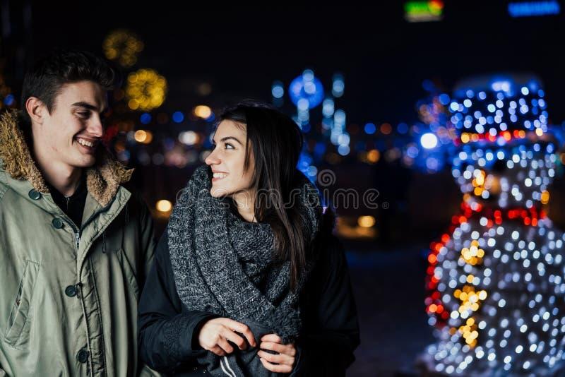 Ritratto di notte di una coppia felice che sorride godendo dei aoutdoors della neve e di inverno Gioia di inverno Emozioni positi immagine stock libera da diritti