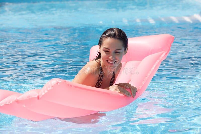 Ritratto di nuoto femminile soddisfatto divertente nella piscina con aiuto del materasso rosa dell'acqua, rilassantesi con gli oc immagini stock libere da diritti