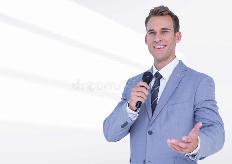 Ritratto di parlare pubblico dell'uomo d'affari sul microfono contro fondo bianco immagini stock