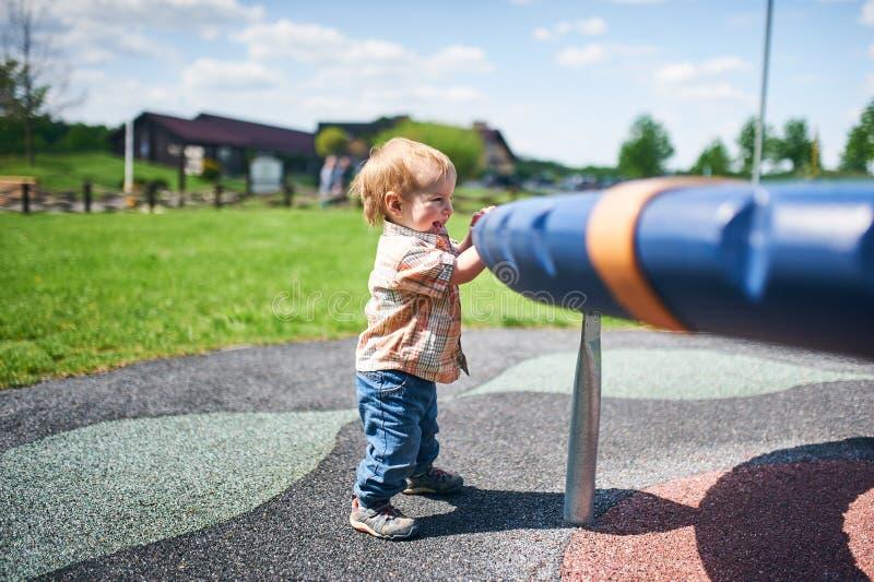 Ritratto di piccola condizione sorridente felice del ragazzo del bambino vicino alle oscillazioni al campo da giuoco fuori il gio immagini stock