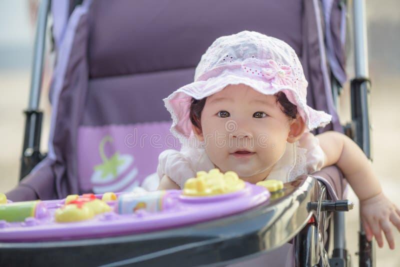 Ritratto di piccola neonata asiatica dolce che si siede in passeggiatore immagine stock