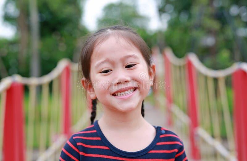 Ritratto di piccola ragazza asiatica sorridente del bambino che vi esamina nel giardino all'aperto immagini stock