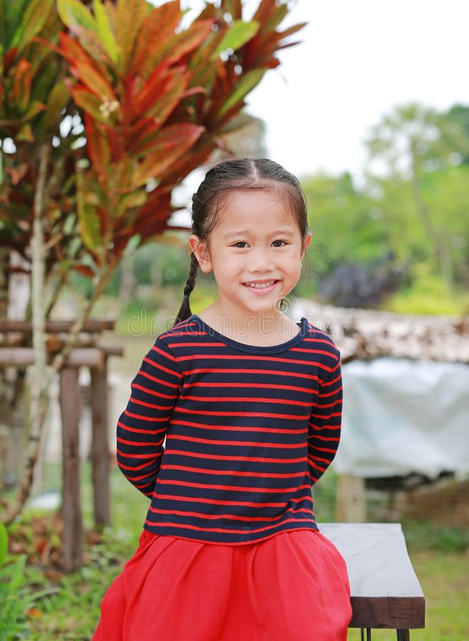 Ritratto di piccola ragazza asiatica sorridente del bambino che vi esamina nel giardino all'aperto immagini stock libere da diritti