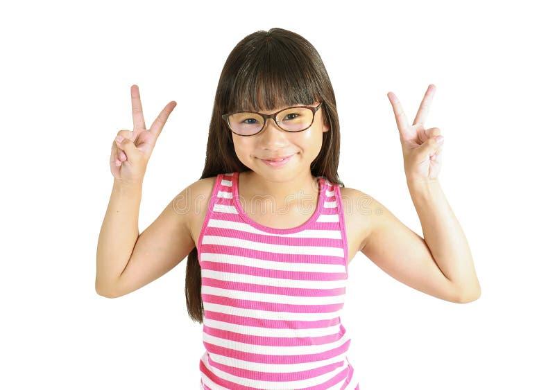 Ritratto di piccola ragazza asiatica sveglia con il segno di combattimento immagini stock libere da diritti
