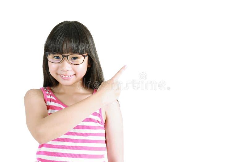 Ritratto di piccola ragazza asiatica sveglia con la sua mano che indica su immagine stock libera da diritti