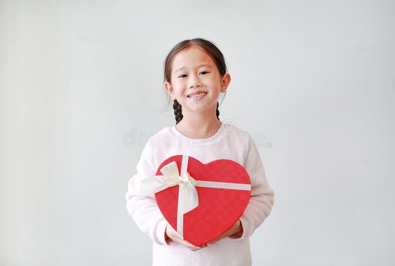 Ritratto di piccola ragazza asiatica sveglia del bambino che giudica il contenitore di regalo rosso del cuore isolato su fondo bi immagini stock