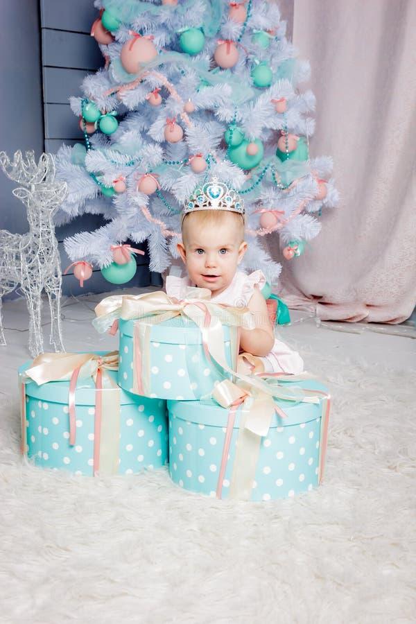 Ritratto di piccola ragazza bionda europea sveglia di principessa con una corona in regali d'apertura di un bello vestito in uno  fotografia stock libera da diritti
