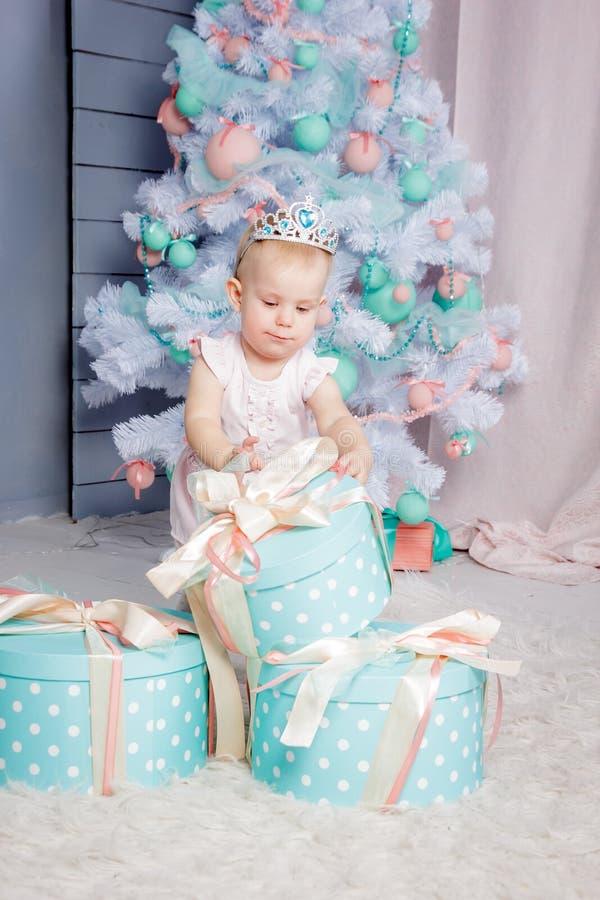 Ritratto di piccola ragazza bionda europea sveglia di principessa con una corona in regali d'apertura di un bello vestito in uno  fotografia stock