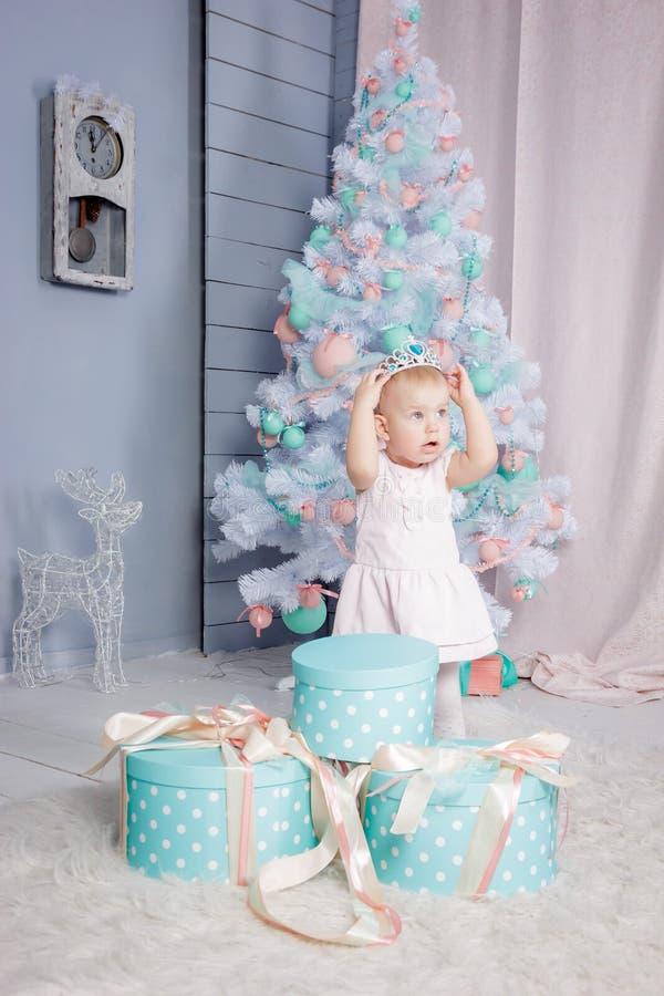 Ritratto di piccola ragazza bionda europea sveglia di principessa con una corona in regali d'apertura di un bello vestito in uno  immagini stock