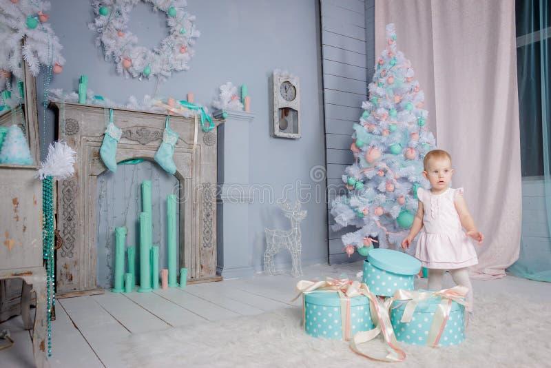 Ritratto di piccola ragazza bionda europea sveglia di principessa con una corona in regali d'apertura di un bello vestito in uno  fotografie stock libere da diritti
