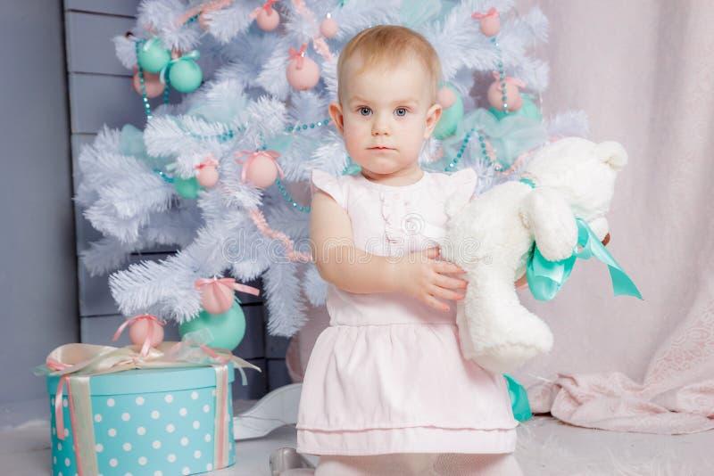 Ritratto di piccola ragazza bionda europea sveglia di principessa con una corona in regali d'apertura di un bello vestito in uno  immagini stock libere da diritti