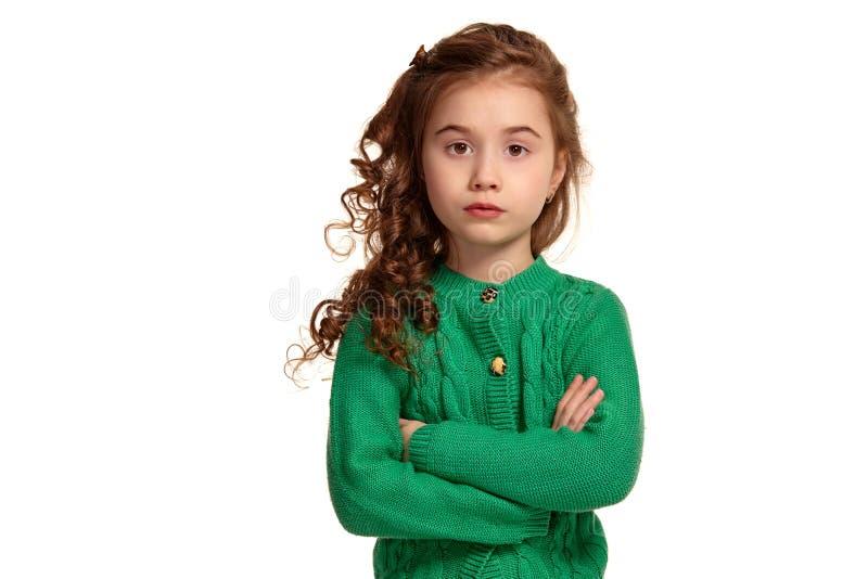 Ritratto di piccola ragazza castana con una posa dei capelli lunghi e ricci isolata su fondo bianco fotografia stock