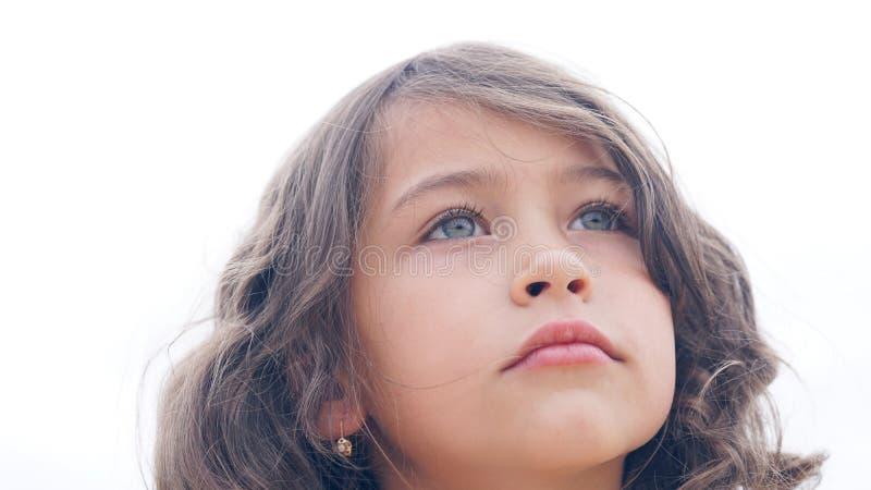 Ritratto di piccola ragazza castana riccia sulla spiaggia di estate Bambina che esamina la distanza con lo sci bianco dentro fotografia stock