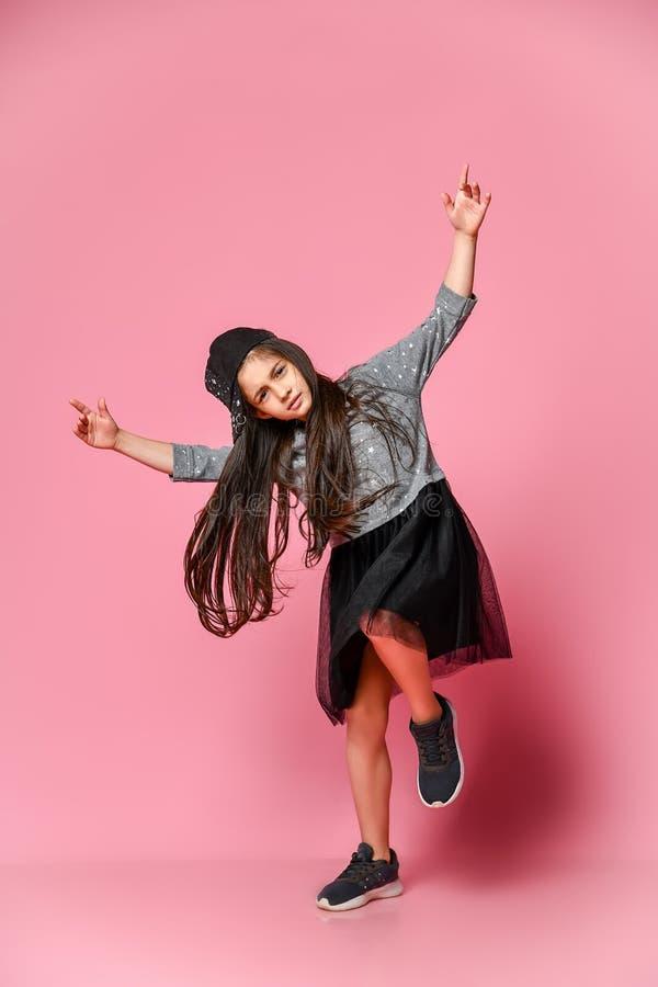 Ritratto di piccola ragazza dei pantaloni a vita bassa in un vestito scuro con un berretto da baseball e le scarpe da tennis, su  fotografia stock