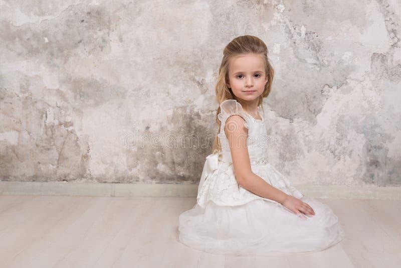 Ritratto di piccola ragazza sorridente attraente in un vestito bianco con capelli arricciati contro lo sfondo di una parete di le fotografie stock