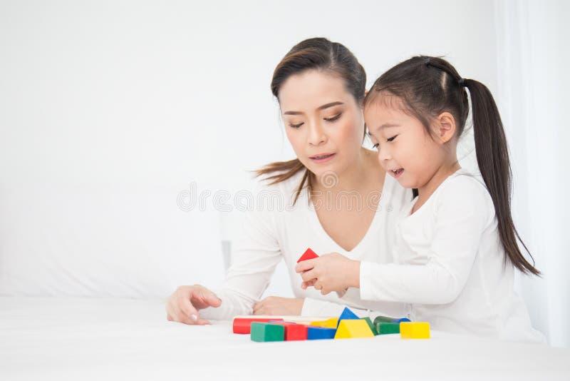 Ritratto di piccola ragazza sveglia asiatica che gioca i blocchi variopinti con sua madre sopra fondo bianco fotografia stock