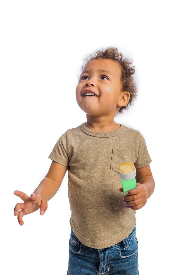 Ritratto di piccolo bambino dalla carnagione scura con capelli ricci che cerca e che sorride mentre tenendo una bottiglia delle b fotografie stock libere da diritti