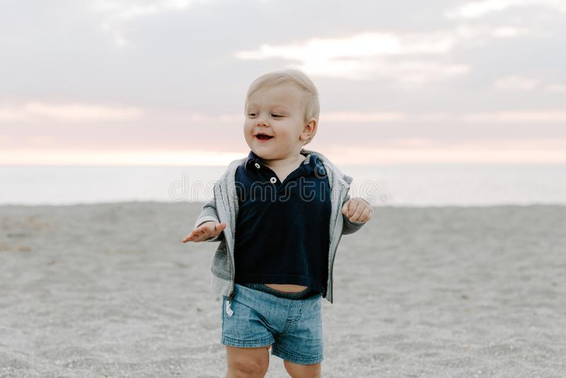 Ritratto di piccolo bambino sveglio del neonato che gioca e che esplora nella sabbia alla spiaggia durante l'esterno di tramonto  immagini stock libere da diritti