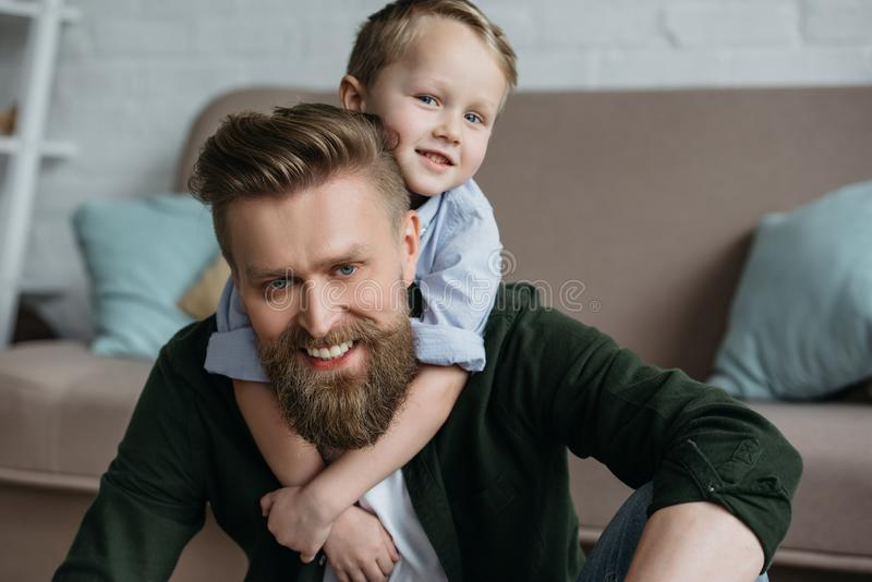 ritratto di piccolo figlio che abbraccia padre barbuto sorridente fotografie stock