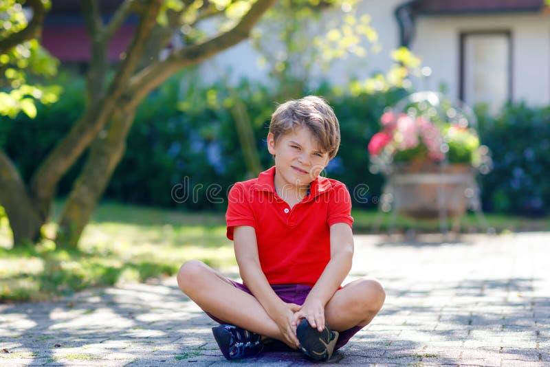 Ritratto di piccolo ragazzo fresco del bambino che si siede sulla terra il giorno soleggiato in cortile domestico Bambino in buon immagini stock