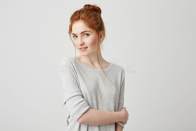 Ritratto di posa sorridente della bella ragazza tenera della testarossa esaminando macchina fotografica sopra fondo bianco immagini stock