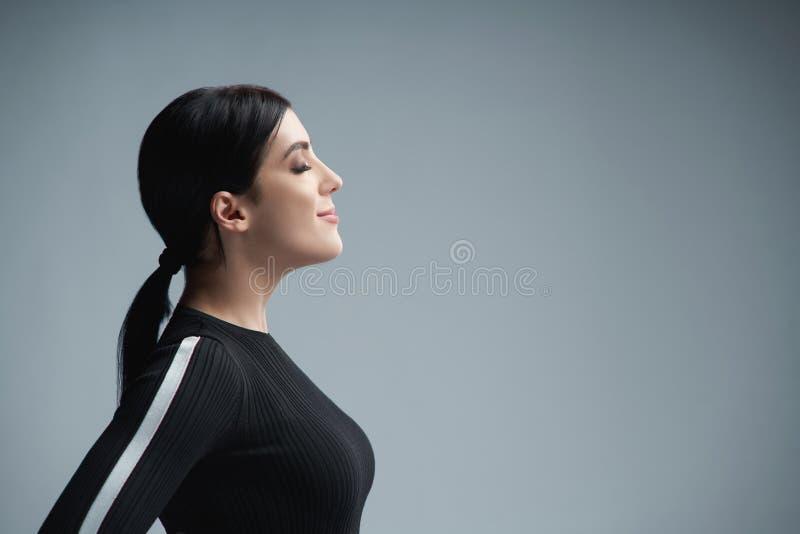 Ritratto di profilo del primo piano della donna sicura con gli occhi chiusi fotografia stock