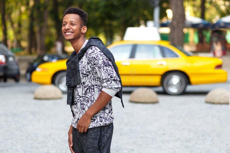Ritratto di profilo di un giovane divertente in abbigliamento casual, camminante nel tempo di giorno, sul fondo vago della via immagini stock libere da diritti