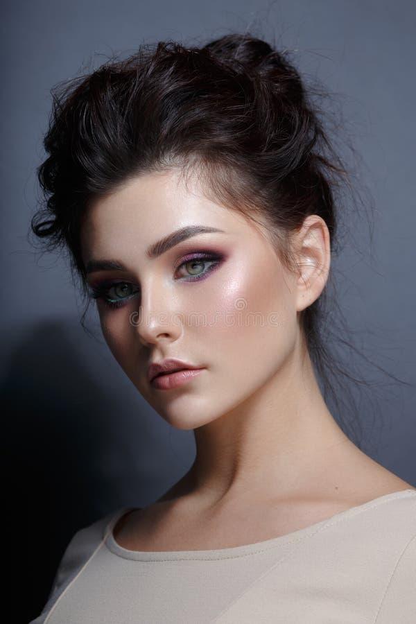 Ritratto di profilo di una donna graziosa con trucco del superbe, esaminante macchina fotografica Vista verticale fotografia stock libera da diritti