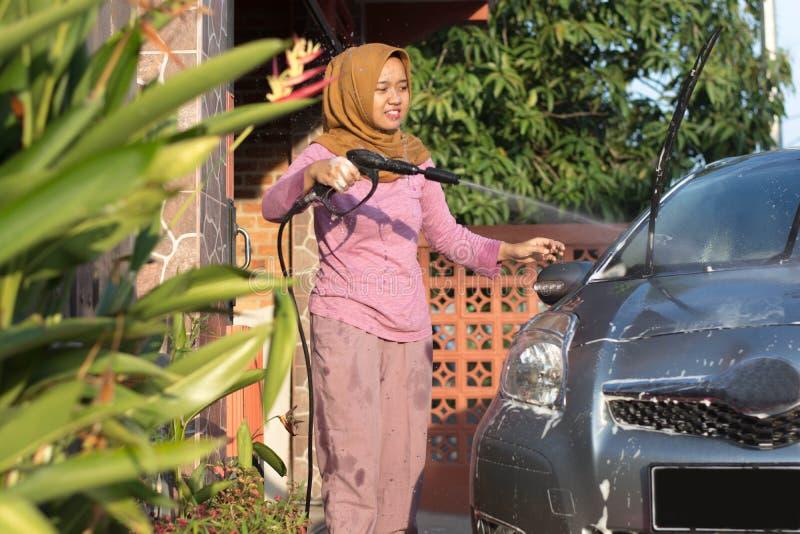 Ritratto di pulizia felice dell'automobile delle donne del hijab - rimuovendo il sapone con acqua, facendo uso di un tubo flessib fotografie stock libere da diritti