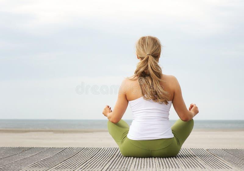 Ritratto di retrovisione della giovane donna che si siede alla spiaggia nella posa di yoga fotografie stock