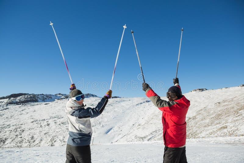 Ritratto di retrovisione di una coppia che alza i pali di sci su neve fotografia stock libera da diritti