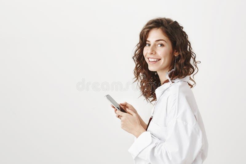 Ritratto di riuscita donna di affari caucasica che sta nel profilo, tenente smartphone e sorridente alla macchina fotografica, es fotografie stock libere da diritti