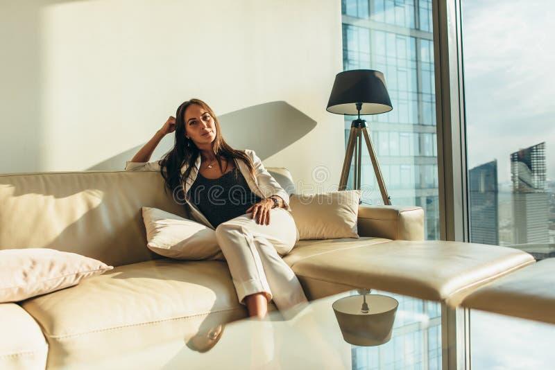 Ritratto di riuscita donna di affari che indossa vestito convenzionale elegante che si siede sul sofà di cuoio che si rilassa dop fotografie stock