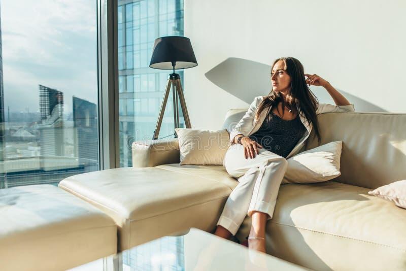 Ritratto di riuscita donna di affari che indossa vestito convenzionale elegante che si siede sul sofà di cuoio che si rilassa dop fotografia stock
