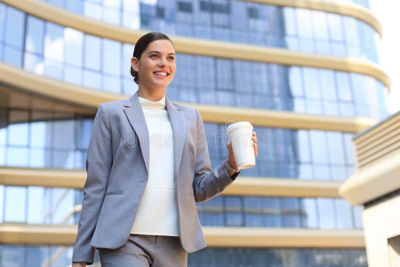 Ritratto di riuscita donna di affari che va lavorare con caffè che cammina vicino all'edificio per uffici sulla via della città fotografia stock