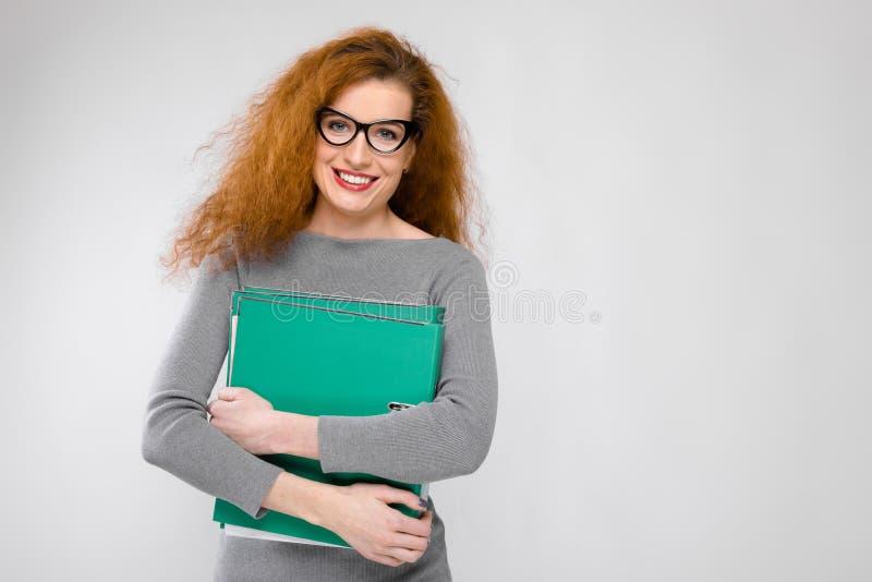 Ritratto di riuscita giovane donna sorridente felice della bella testarossa in vestiti grigi in vetri che tengono le cartelle su  immagine stock