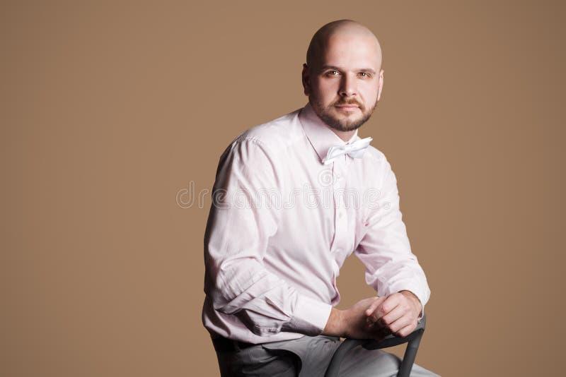 Ritratto di riuscito uomo calvo barbuto bello nella s rosa-chiaro immagini stock libere da diritti