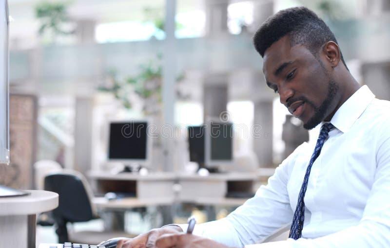 Ritratto di riuscito uomo d'affari afroamericano che si siede allo scrittorio con il computer in ufficio fotografie stock libere da diritti