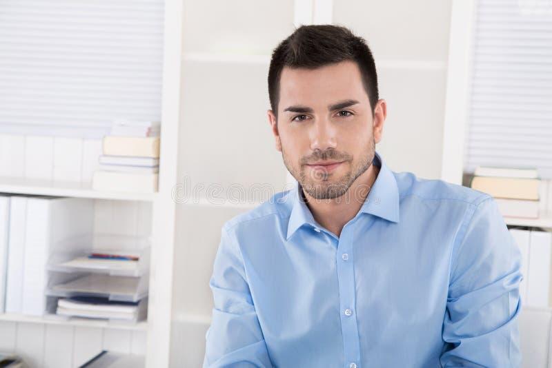 Ritratto di riuscito uomo d'affari in camicia blu che si siede in ciao immagine stock