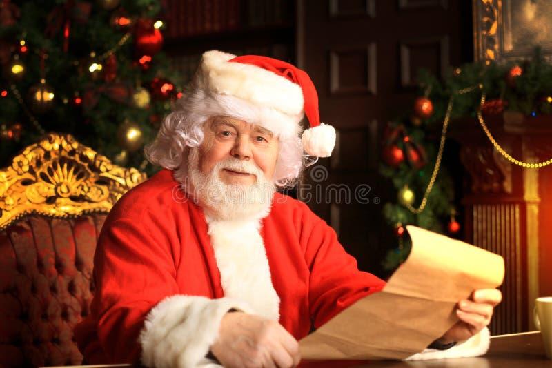 Ritratto di Santa Claus felice che si siede alla sua stanza a casa vicino all'albero di Natale e che legge la lettera o la lista  immagine stock libera da diritti