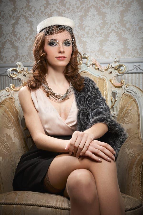 Ritratto di seduta della giovane donna graziosa nel retro stile immagini stock libere da diritti