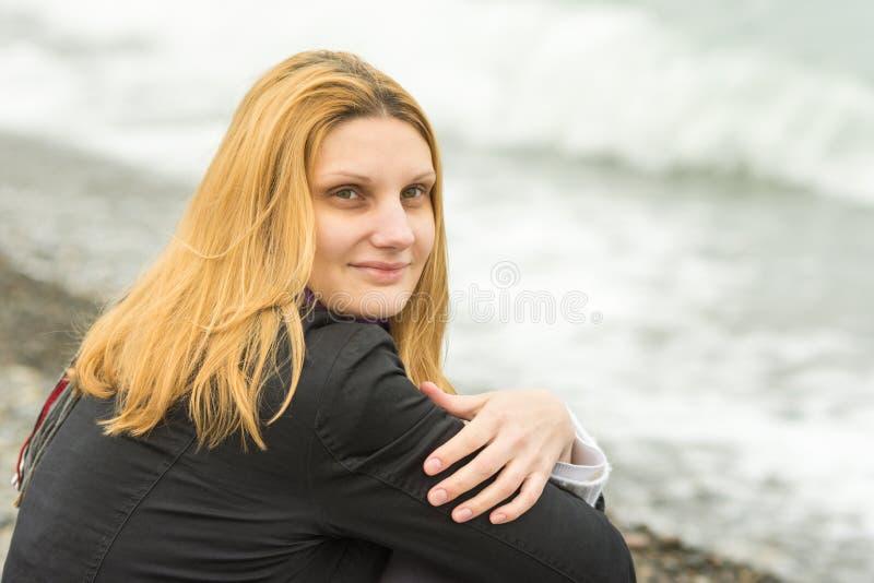 Ritratto di seduta sulla ragazza misteriosamente sorridente della spiaggia in tempo nuvoloso fotografia stock libera da diritti