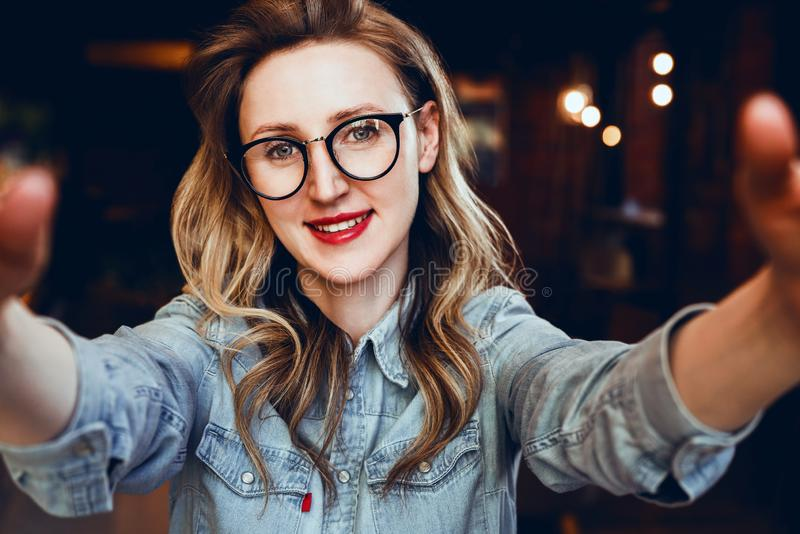 Ritratto di Selfie di giovane donna sorridente che si siede in caffè La ragazza dei pantaloni a vita bassa in vetri d'avanguardia fotografia stock