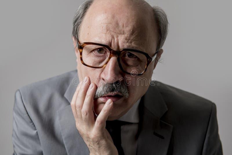Ritratto di sguardo triste e depresso senior calvo dell'uomo di affari 60s divertente e sudicio nell'espressione del fronte di em fotografia stock
