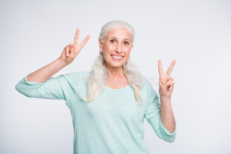 Ritratto di signora adorabile che fa i v-segni che sembrano il pullover d'uso dell'alzavola isolato sopra fondo bianco fotografia stock