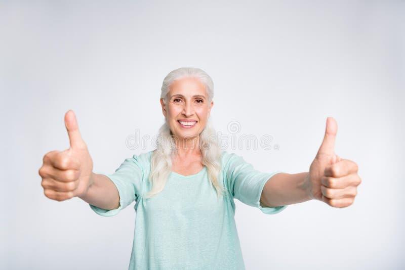 Ritratto di signora allegra che mostra il pullover d'uso sorridente dell'alzavola di pubblicità del pollice-su isolato sopra fond fotografie stock