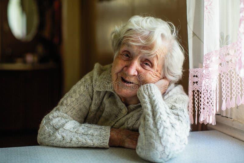 Ritratto di signora anziana che si siede alla tavola immagine stock